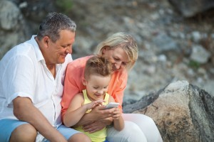 Happy grandparents and grandson with smartphone outdoor. Grandmother and grandfather watching the boy playing with mobile